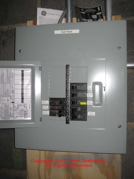 The completed GE sub-panel with all circuits labeled as required by the National Electrical Code. Yellow tape on the circuit breaker helps homeowner choose circuits