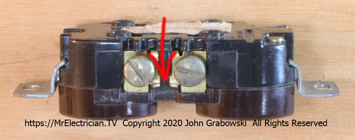A duplex electrical receptacle on its side showing a cut tab