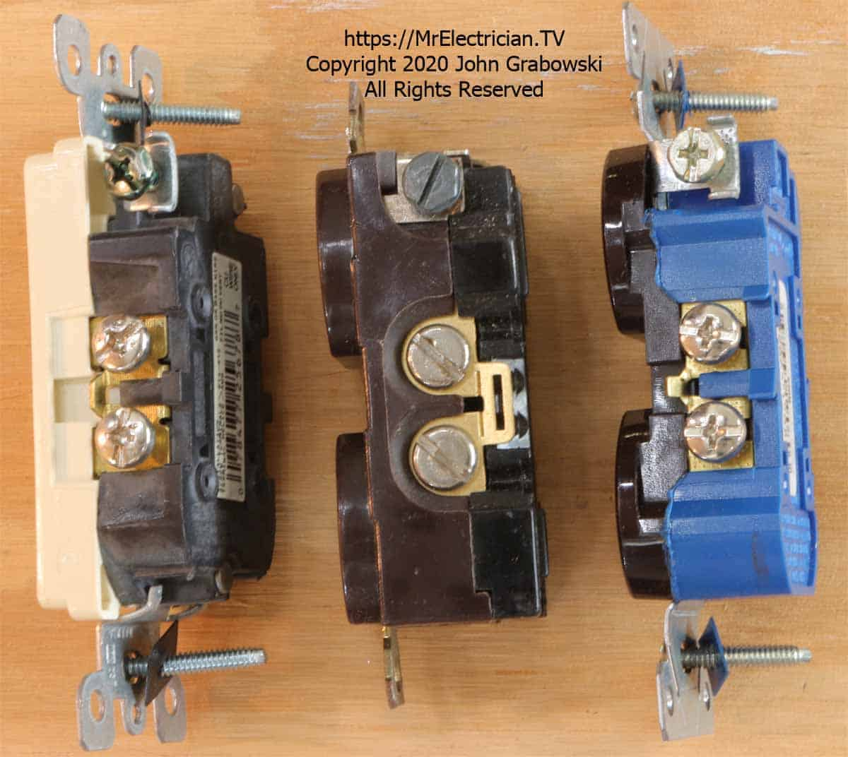 Three duplex electrical receptacle outlets on their side showing the break-off tabs for creating a split receptacle