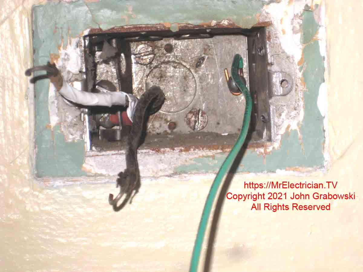 A very old style electrical receptacle outlet that could accommodate two types of plugs