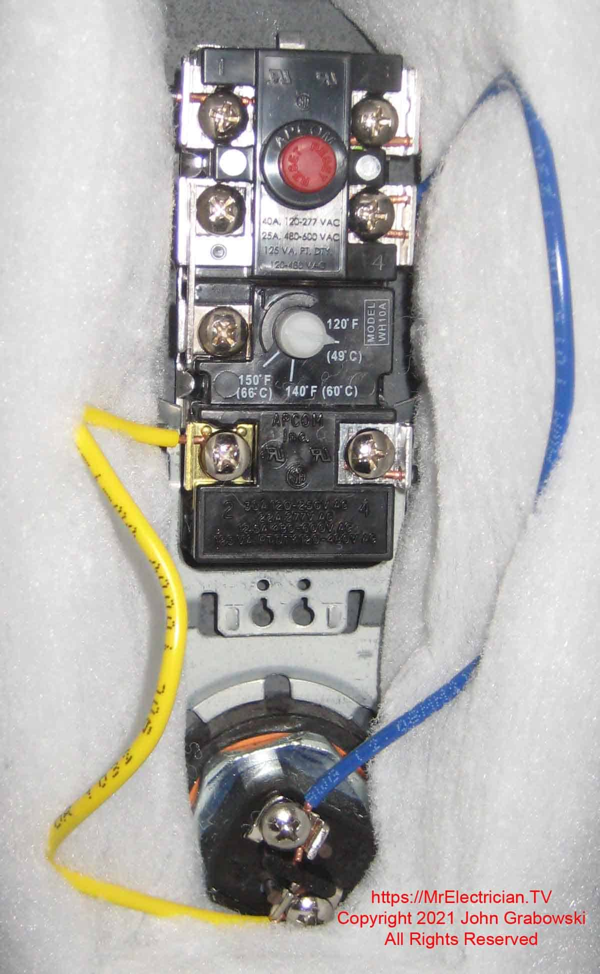 The upper thermostat and heating element of an electric water heater